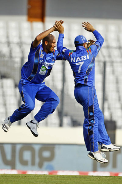 Mirwais Ashraf and Mohammad Nabi leap in celebration during their Asia Cup between Afghanistan and Sri Lanka, Asia Cup, Mirpur on Monday. (AP)