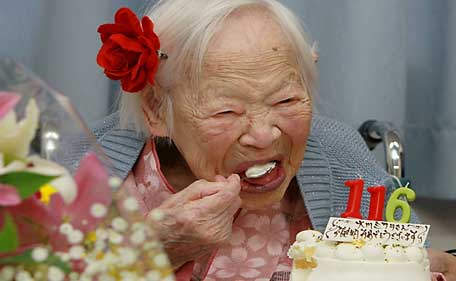 Misao Okawa, the world's oldest woman, eats her birthday cake as she celebrates her 116th birthday at a nursing home in Osaka on March 5, 2014.  The world's oldest woman was celebrating her 116th birthday on March 5 in a Japanese nursing home with a cake and candles.  (AFP)