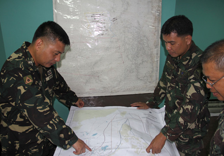 In this photo released by the Armed Forces of the Philippines, Western Command PIO, Filipino government troopers look at a map as they continue the search for the missing plane of Malaysian Airlines at Antonio Bautista Air Base in Puerto Princesa City, Palawan province after conducting air search for the missing plane of Malaysian Airlines on Saturday March 8, 2014. Search and rescue crews across Southeast Asia scrambled to find a Malaysia Airlines Boeing 777 that disappeared from air traffic control screens over waters between Malaysia and Vietnam early Saturday with 239 people aboard. (AP)