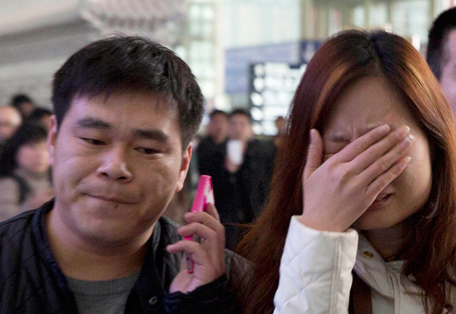A woman cries at the arrival hall of the International Airport in Beijing, China, Saturday, March 8, 2014. Relatives and friends were arriving at Beijing airport for news after a Malaysia Airlines Boeing 777-200 was reported missing on a flight from Kuala Lumpur to Beijing Saturday. (AP)