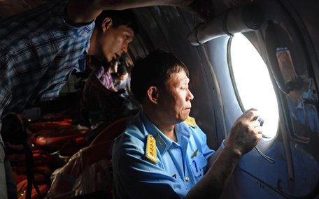 This picture taken from aboard a flying Soviet-made AN-26 used as a search aircraft by Vietnamese Air Force to look for missing Malaysia Airlines flight MH370, shows an officer (R) and a reporter looking out the window during search operations over the southern seas off Vietnam on March 9, 2014. Malaysia on March 9 launched a terror probe into the disappearance of a Malaysian Airlines passenger jet carrying 239 people the day before, investigating suspect passengers who boarded with stolen passports, as relatives begged for news of their loved ones. The United States sent the FBI to investigate after Malaysia Airlines flight MH370 vanished from radar early on March 8 somewhere at sea between Malaysia and Vietnam, but stressed there was no evidence of terrorism yet.  (AFP)
