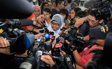 In this March 8, 2014 photo, a family member of passengers aboard a missing Malaysia Airlines plane is mobbed by journalists at Kuala Lumpur International Airport in Sepang, outside Kuala Lumpur, Malaysia. More than a day and a half has passed since the Boeing 777 jet disappeared from radar contact in the first hour of a six-hour flight from Kuala Lumpur, Malaysia to China's capital. From France to Australia and China, families and friends are enduring an agonizing wait for news about flight MH370. (AP)