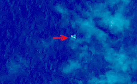 "This handout photo provided on March 13, 2014 by the China Center for Resources Satellite Data and Application (CCRSDA) and released by the website of the State Administration of Science, Technology and Industry for the National Defence of China, shows a satellite image taken from space, illustrating objects in a ""suspected crash sea area"" in the South China Sea on March 9, 2014, thought to possibly be from the missing Malaysia Airlines flight MH370 which went missing early on March 8, 2014 after departing Kuala Lumpur for Beijing.  China said its satellites have detected three large floating objects in a suspected crash site near where the missing Malaysian jet lost contact, the latest twist in a hunt which entered its sixth day on March 13, 2014.   NOTE: Red arrow on image originated from source. (AFP)"