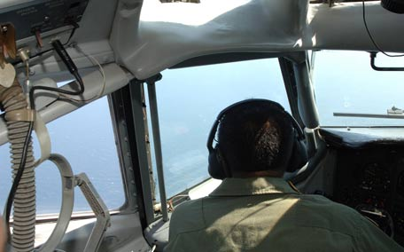 Indonesian Air Force pilot aboard an Indonesian Air Force military surveillance aircraft over the Malacca Strait, a sea  passageway between Indonesia and Malaysia, while searching for the missing Malaysia Airlines flight MH370 plane. (AFP)