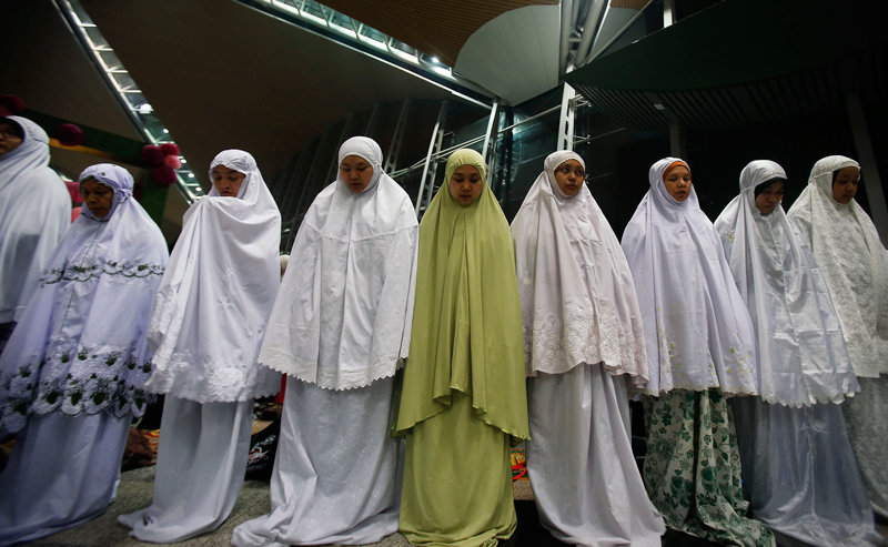 Muslim women offer prayers at the Kuala Lumpur International Airport for the missing Malaysia Airlines jetliner MH370, Thursday, March 13, 2014 in Sepang, Malaysia. Planes sent Thursday to check the spot where Chinese satellite images showed possible debris from the missing Malaysian jetliner found nothing, Malaysia's civil aviation chief said, deflating the latest lead in the six-day hunt. The hunt for the missing Malaysia Airlines flight 370 has been punctuated by false leads since it disappeared with 239 people aboard about an hour after leaving Kuala Lumpur for Beijing early Saturday. (AP)