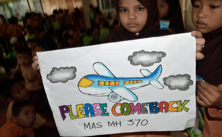 An Indonesian student displays a message expressing prayers and well-wishes for passengers of the missing Malaysia Airlines (MAS) flight MH370, in Medan, North Sumatra on March 15, 2014. Malaysia's leader on March 15 said communications aboard a missing jet were switched off and its course deliberately changed by someone on board before the aircraft disappeared a week ago, but stopped short of saying it had been hijacked. (AFP)
