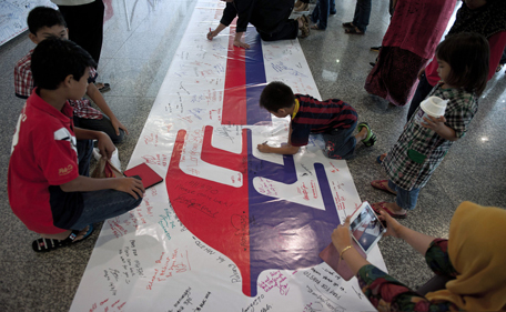 Visitors write on a banner carrying messages for the passengers of missing Malaysia Airlines flight MH370 at Kuala Lumpur International Airport (KLIA) in Sepang, outside Kuala Lumpur on March 16, 2014. Investigators probing the disappearance of Malaysia Airlines MH370 piloted an identical Boeing 777-200 on the missing plane's suspected flight path, in a re-enactment confirming their belief that it banked west, a senior Malaysian military official said on March 16. (AFP)