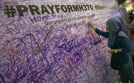 A woman leaves a message for passengers aboard a missing Malaysia Airlines plane, at a shopping mall in Petaling Jaya, near Kuala Lumpur, Malaysia. (AP)
