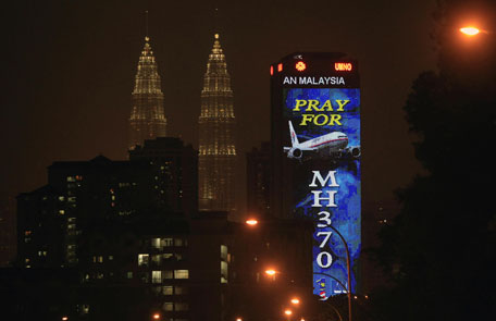 """An office building is illuminated with LED lights displaying """"Pray for MH370"""" next to Malaysia's landmark Petronas Twin Towers in Kuala Lumpur, Malaysia, Wednesday, March 19, 2014. Countless theories have surfaced about the disappearance of Malaysia Airlines Flight 370 nearly two weeks ago. (AP)"""