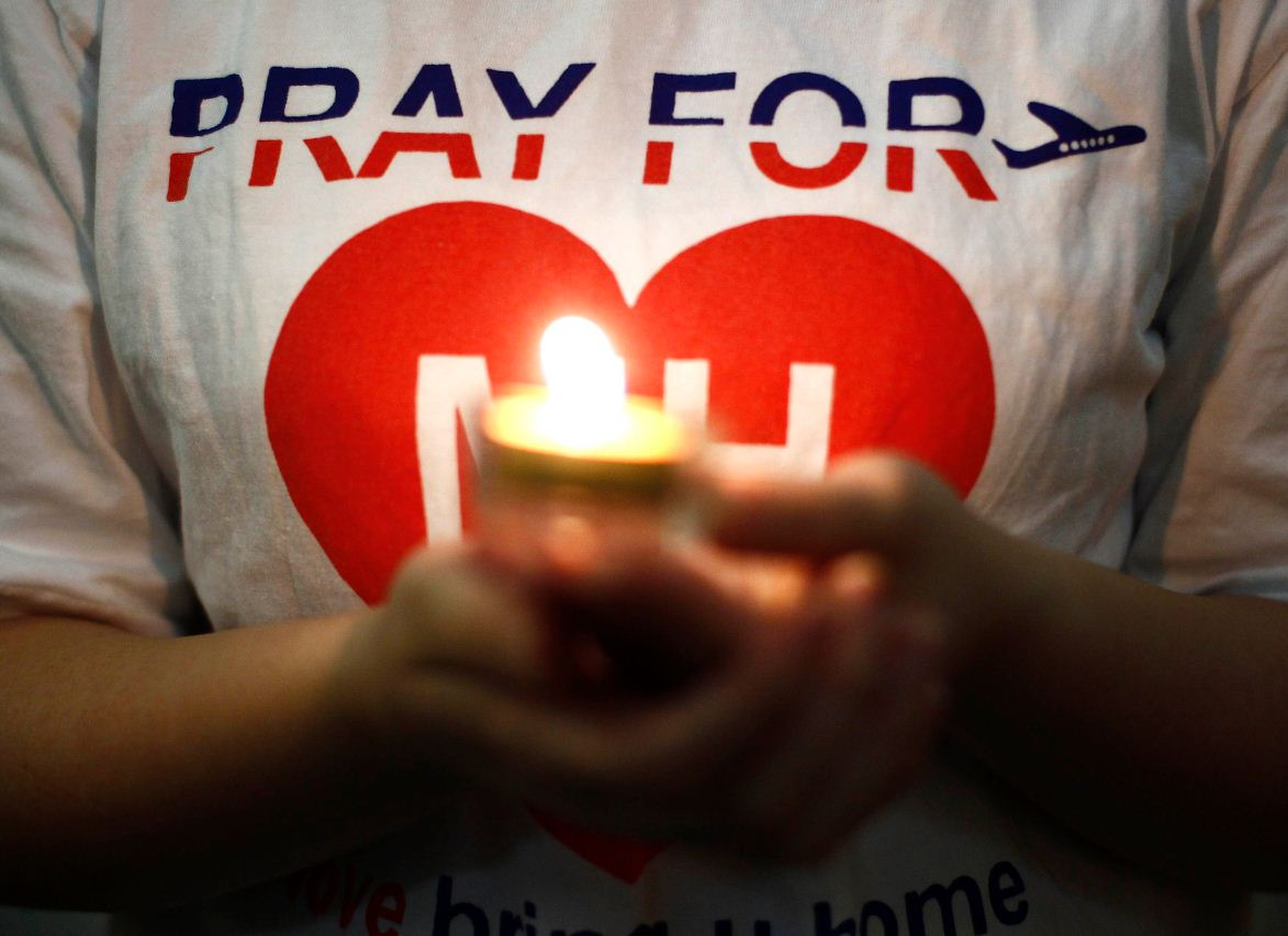 A woman holds a candle during a special prayer for passengers onboard the missing Malaysia Airlines Flight MH370 at the Chinese Assembly Hall in Kuala Lumpur March 19, 2014. (REUTERS)