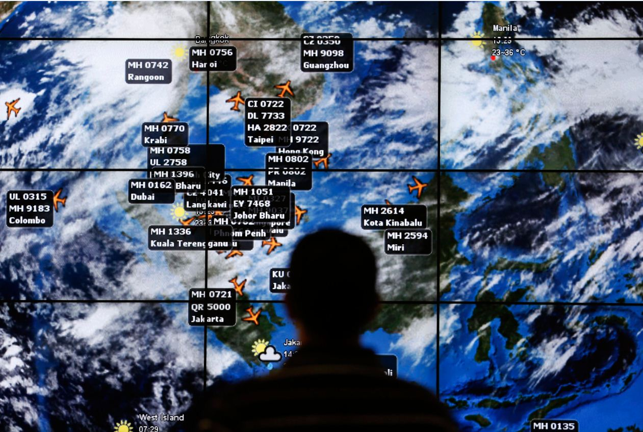 A man watches a large screen showing different flights at the departure hall of Kuala Lumpur International Airport in this 2014 file photo. (REUTERS)