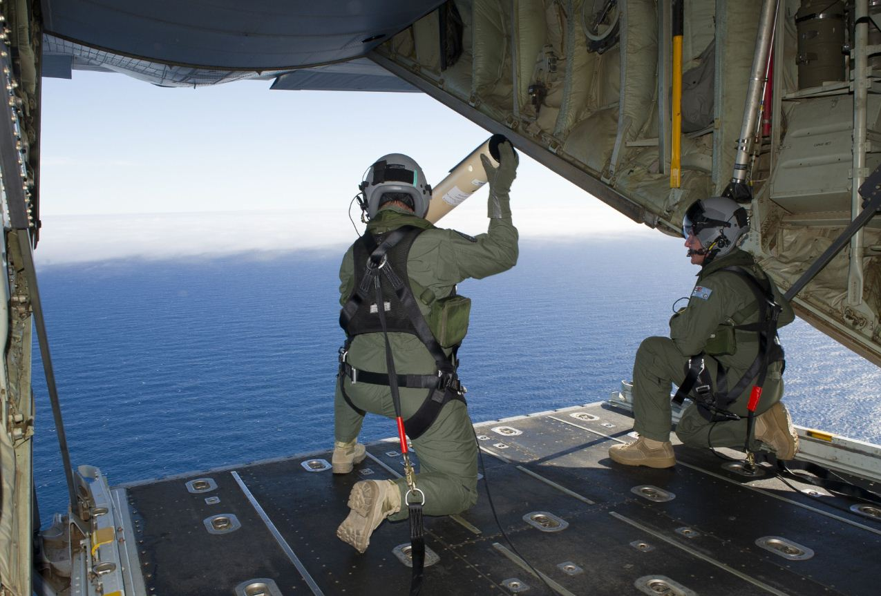 A photo taken on March 20, 2014, shows Royal Australian Air Force Loadmasters, Sergeant Adam Roberts (L) and Flight Sergeant John Mancey (R), preparing to launch a Self Locating Data Marker Buoy from a C-130J Hercules aircraft in the southern Indian Ocean as part of the Australian Defence Force's assistance to the search for Malaysia Airlines flight MH370.  Australia resumed the search 21 March for possible wreckage from a missing Malaysian jetliner in a remote, storm-swept stretch of the Indian Ocean, hoping for better weather as spotters seek to identify the objects shown on grainy satellite images. (AFP)