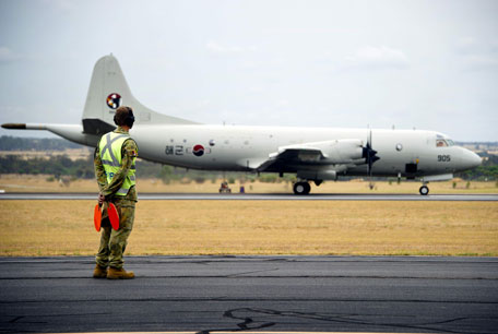 A Republic of Korea Navy (ROKN) P3-C Orion aircraft is watched by an official as it arrives at the Royal Australian Air Force (RAAF) Base Pearce, located north of Perth, to participate in the search for missing Malaysia Airlines Flight MH370 in this picture released by the Australian Defence Force March 27, 2014. Severe weather on Thursday halted an air and sea search for a Malaysia Airlines passenger jet presumed crashed in the southern Indian Ocean, frustrating hopes of finding what new satellite images showed could be a large debris field. (REUTERS)
