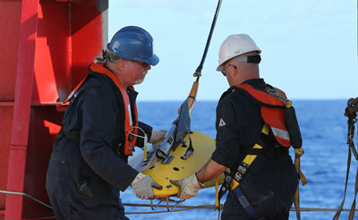 """Phoenix Internaional personnel, Mike Unzicker and Chris Minor deploy the towed pinger locator off the deck of the Australian Defence Vessel Ocean Shield in the southern Indian Ocean during the search for the flight data recorder and cockpit voice recorder of the missing Malaysian Airlines flight MH370 in this picture released by the Australian Defence Force April 5, 2014. The search for missing Malaysia Airlines flight MH370 in remote seas off Australia headed underwater, with a U.S. Navy high tech """"black box"""" locator deployed for the first time as the battery life of the cockpit data recorder dwindles. A total of 20 aircraft and ships were again scouring a massive area in the Indian Ocean some 2,000 km (1,200 miles) west of Perth, where investigators believe the Boeing 777 carrying 239 people came down. (Reuters)"""