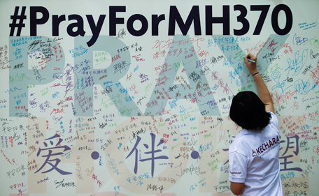 A woman writes a message on a board for family members of passengers onboard the missing Malaysia Airlines Flight MH370 at the Malaysian Chinese Association (MCA) headquarters in Kuala Lumpur April 6, 2014. International search planes and ships are heading to an area where a Chinese ship twice heard what could be signals from MH370's black box locators, Australian search authorities said on Sunday. (REUTERS)