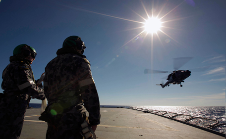 """Crew aboard the Australian Navy ship HMAS Success watch as a helicopter participates in a Replenishment at Sea evolution with the Royal Malaysian Navy ship KD LEKIU in the southern Indian Ocean during the continuing search for the missing Malaysian Airlines flight MH370 in this picture released by the Australian Defence Force April 7, 2014. Australian officials said on Monday signals picked up by a black box detector attached to an Australian ship searching for Malaysia Airlines Flight MH370 were consistent with aircraft flight recorders. """"Clearly, this is a most promising lead,"""" Angus Houston, head of the Australian agency coordinating the search, told a news conference in Perth. Houston, a retired air chief marshal, said two signals had been detected off Australia's northwest coast. Confirmation of whether the signals were emitted from the Malaysian plane, missing since March 8 with 239 people on board, could take several days, Houston said. (REUTERS)"""
