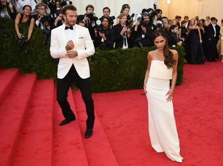 David Beckham looks on as his wife Victoria Beckham poses at the Metropolitan Museum of Art's. (AP)