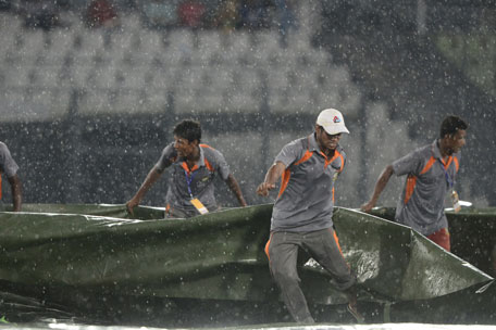 Groundsmen cover the field as rain stops play during the one day international between India and Bangladesh at the Sher-e-Bangla National Cricket Stadium in Dhaka on June 15, 2014. (AFP)