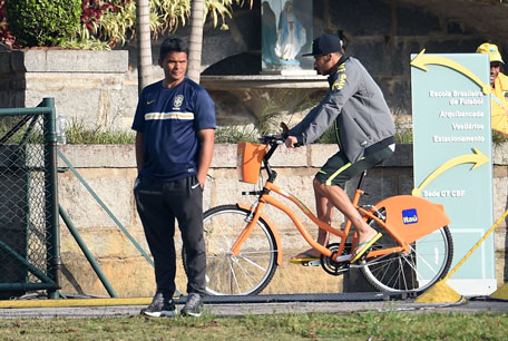 Brazil's forward Neymar rides a bicycle ahead of a training session at the Granja Comary training complex in Teresopolis during the 2014 FIFA World Cup football tournament on July 1, 2014. (AFP)