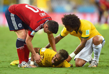 Neymar of Brazil lies on the field after a challenge as teammate Marcelo and James Rodriguez of Colombia look on during the 2014 FIFA World Cup Brazil Quarter Final match between Brazil and Colombia at Castelao on July 4, 2014 in Fortaleza, Brazil. (GETTY)