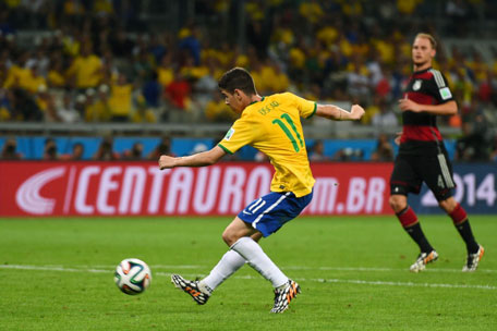 Oscar of Brazil shoots and scores his team's first goal during the 2014 FIFA World Cup Brazil Semi Final match between Brazil and Germany at Estadio Mineirao on July 8, 2014 in Belo Horizonte, Brazil. (GETTY)