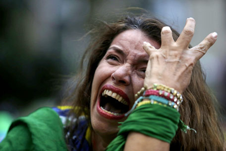 A Brazil soccer fan cries as Germany scores against her team at a semifinal World Cup match as she watches the game on a live telecast in Belo Horizonte, Brazil, Tuesday, July 8, 2014. (AP)