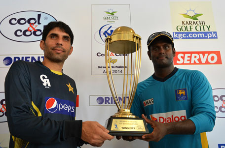 Pakistan cricket team captain Misbah-ul-Haq (left) and Sri Lankan cricket team captain Angelo Mathews pose with the series' trophy during a press conference at the Galle International Cricket Stadium in Galle on August 5, 2014. (AFP)