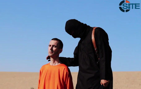 An image grab taken from a video released by 'Daesh' and identified by private terrorism monitor SITE Intelligence Group on September 13, 2014 purportedly shows British aid worker David Haines dressed in orange and on his knees in a desert landscape speaking to the camera before being beheaded by a masked militant (R). (AFP)