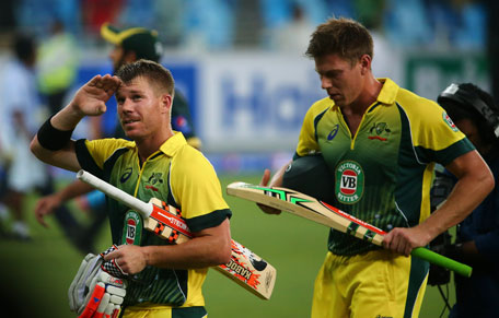 Australian batsman David Warner (left) salutes the crowd as he and teammate James Faulkner leave the pitch at the end of the first International T20 cricket match against Pakistan in Dubai on October 5, 2012. (AFP)