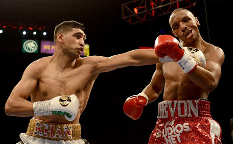 Amir Khan (left) hits Devon Alexander during their welterweight bout at the MGM Grand Garden Arena on December 13, 2014 in Las Vegas, Nevada. (Getty)