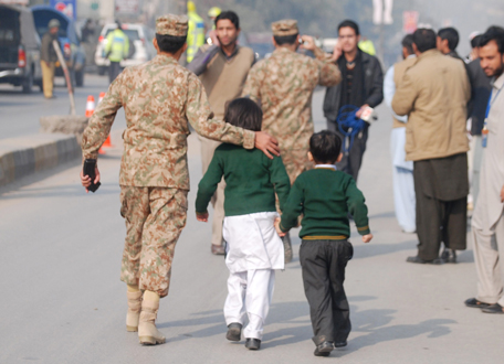 A soldier escorts schoolchildren after they were rescued from the Army Public School that is under attack by Taliban gunmen in Peshawar, December 16, 2014. (Reuters)