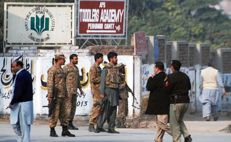 Pakistani security forces takes up a positions on a road leading to the Army Public School that is under attack by Taliban gunmen in Peshawar, December 16, 2014. Taliban gunmen in Pakistan took hundreds of students and teachers hostage on Tuesday in a school in the northwestern city of Peshawar, military officials said.  (REUTERS)