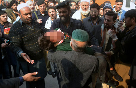Hospital security guards carry a students injured in the shootout at a school under attacked by Taliban gunmen in Peshawar, Pakistan,Tuesday, Dec 16, 2014.  (AP)