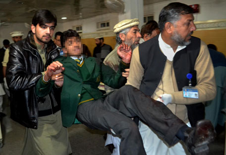 Pakistani volunteers carry a student injured in the shootout at a school under attack by Taliban gunmen, at a local hospital in Peshawar, Pakistan,Tuesday, Dec. 16, 2014. (AP)