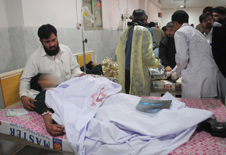 A man comforts his son, who was injured during an attack by Taliban gunmen on the Army Public School, at Lady Reading Hospital in Peshawar, December 16, 2014. Taliban gunmen in Pakistan took hundreds of students and teachers hostage on Tuesday in a school in the northwestern city of Peshawar, military officials said. REUTERS