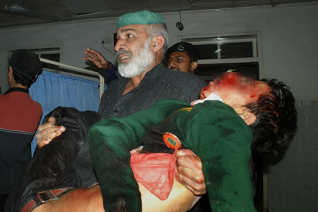 A Pakistani man carries an injured student at a hospital following an attack by Taliban gunmen on a school in Peshawar on December 16, 2014. Taliban insurgents killed at least 130 people, most of them children, after storming an army-run school in Pakistan December 16 in one of the country's bloodiest attacks in recent years. AFP