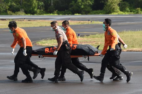 Members of an Indonesian search and rescue team carry the body of a victim recovered in the search for wreckage of AirAsia flight QZ8501, lost over the Java Sea, in Pangkalan Bun, the town with the nearest airstrip to the crash site, in Central Kalimantan on January 2, 2015. Relatives held the first funeral for a victim of AirAsia Flight QZ8501 on January 1 as bad weather hampered efforts to locate the wreckage of the plane which crashed in the sea off Borneo with 162 aboard on December 28.  (AFP)