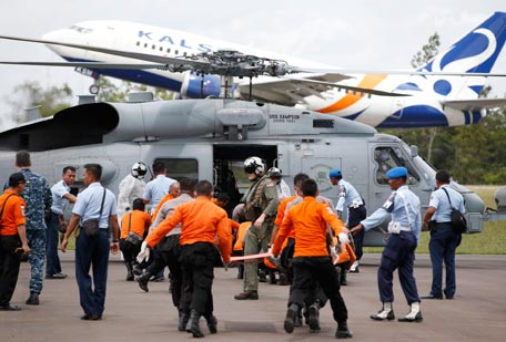 A passenger plane lands (rear) as crew members from a U.S. Navy helicopter from the USS Sampson unload the remains of passengers from AirAsia QZ8501, recovered from the sea, at the airport in Pangkalan Bun, Central Kalimantan January 2, 2015. International experts with sophisticated acoustic detection gear joined teams scouring the sea for the wreck of the Indonesia AirAsia passenger jet on Friday, but bad weather was again hindering the hunt for the plane's black box flight recorders. (REUTERS)