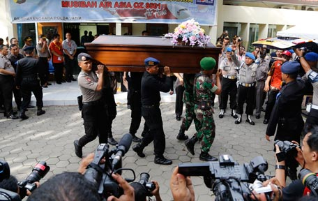 Indonesian soldiers and police officers carry a coffin containing the body of Kevin Alexander Soetjipto, one of the victims of AirAsia Flight QZ 8501 during the handover to the family at Bhayangkara Police Hospital in Surabaya, East Java, Indonesia, Friday, Jan. 2, 2015. The investigation into the AirAsia crash has turned to the ocean floor, with more sonar equipment and metal detectors deployed Friday to scour the seabed for wreckage, including the plane's black boxes. (AP)