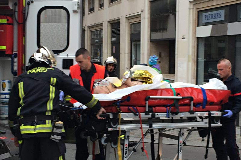 Firefighters carry an injured man on a stretcher in front of the offices of the French satirical newspaper Charlie Hebdo in Paris on January 7, 2015. (AFP)