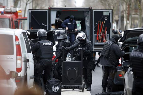 Members of the French national police intervention group (BRI) prepare their gear near the site of a shooting on the morning of January 8, 2015 in Montrouge, south of Paris. A policewoman who was shot by a gunman wearing a bullet-proof vest just outside Paris has died and a second victim is in serious condition, police said on January 8. The man escaped after the attack on Thursday morning, which comes just a day after a deadly Islamist assault on satirical magazine Charlie Hebdo left 12 dead, although no link has yet been established between the two incidents. AFP