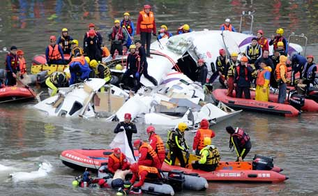 Emergency personnel retrieve the body of a passenger from the wreckage of a TransAsia Airways turboprop ATR 72-600 aircraft after it was crashed in a river, in New Taipei City, February 4, 2015. (Reuters)