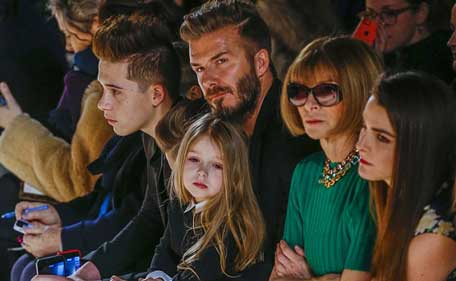 Former England captain David Beckham sits next to U.S. Vogue editor Anna Wintour (2nd R) with his daughter, Harper, on his lap and son Brooklyn (L) during a presentation of the Victoria Beckham Fall/Winter 2015 collection during New York Fashion Week February 15, 2015. (Reuters)
