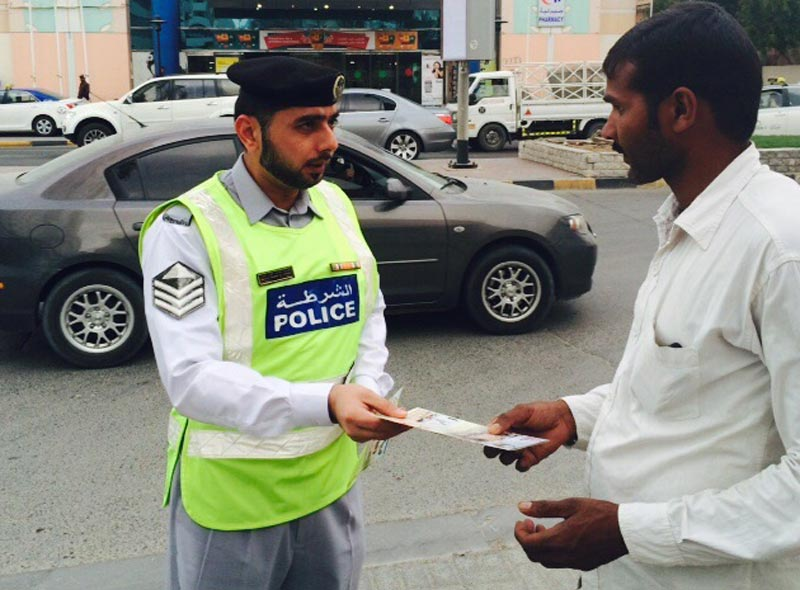 Traffic police distributing leaflets on road safety to pedestrians in Ajman. (Supplied)