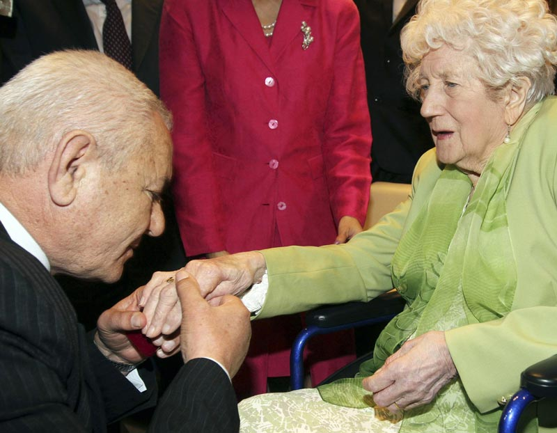 Albanian Xhemil Cala (left) puts the ring of the British flight engineer Sergeant John Thompson, onto the finger of his sister Dorothy Webster, 92, during a ceremony held at the Ministry of Defence in Tirana March 9, 2015. (Reuters)