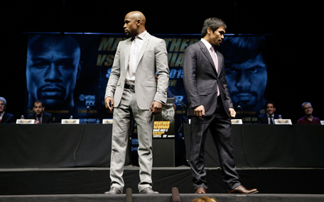 Boxers Floyd Mayweather Jr., left, and Manny Pacquiao, of the Philippines, walk away from each other after posing for photos during a news conference, Wednesday, March 11, 2015, in Los Angeles. The two are scheduled to fight in Las Vegas on May 2. (AP)