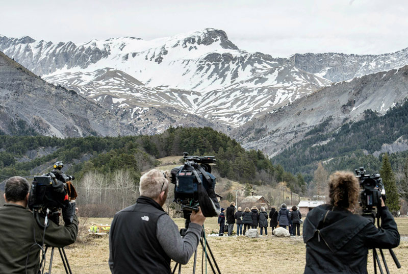 Journalists film as people pay tribute to the victims of a Germanwings flight that crashed in the French Alps, killing all 150 aboard, on March 28, 2015 at a memorial in le Vernet, south-eastern France, near the site of the crash.(AFP)