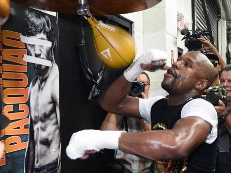 WBC/WBA welterweight champion Floyd Mayweather Jr. hits a speed bag as he works out in front of a poster of WBO welterweight champion Manny Pacquiao with his eyes and mouth taped over at the Mayweather Boxing Club. (AFP/Getty)