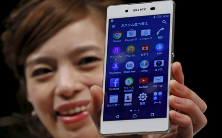 A model poses with Sony's new Xperia Z4 smartphone after a news conference in Tokyo April 20, 2015. Sony Corp on Monday unveiled the new high-end Xperia handset featuring an aluminium frame and a 5.2-inch screen, showing it is still in the smartphone race even as it scales down its struggling mobile operations.    (REUTERS)