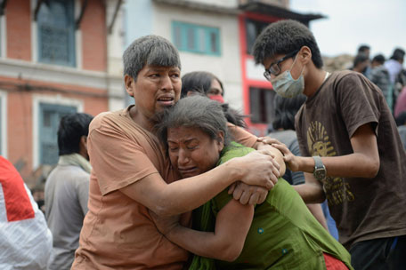 A Nepalese man and woman hold each other in Kathmandu's Durbar Square, a UNESCO World Heritage Site that was severely damaged by an earthquake on April 25, 2015. (AFP)